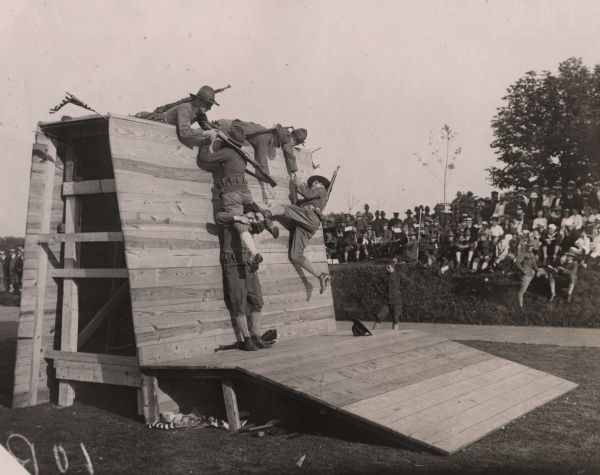 World War I recruits scramble over an obstacle during their training, while others watch in the background.