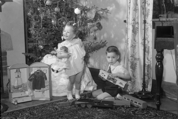"Roger and Mary Sue Mallory, in front of a Christmas Tree, playing with toys their father Lieut. Col. Robert Mallory, stationed in France, sent to them. Roger's train includes a wooden car with the famous World War I slogan, ""40 hommes ou 8 chevaux"". Mary Sue's doll ""Mademoiselle"" came from France with a trunk of clothes. A Christmas tree is in the background."