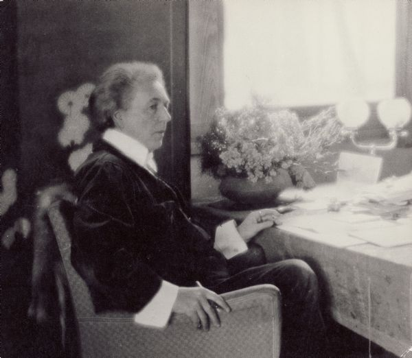 Frank Lloyd Wright sits by a sunlit window in his living room at Taliesin, with papers spread before him on a table.