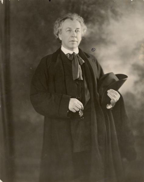 "Frank Lloyd Wright dressed in long, black coat, holding eyeglasses in one hand and a hat in the other. This image prompted Robert Lamp's young cousins to call Wright ""Quaker Oats"" in the 1880's."