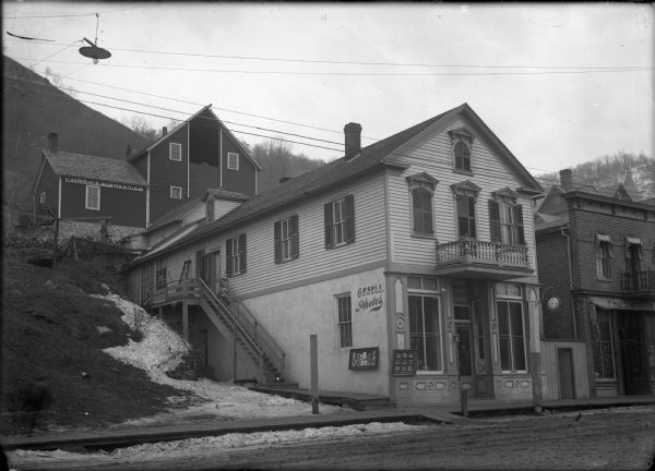 Street with Gesell Photographic Studio, which is built into the side of a bluff, about 1895. His studio was on Main Street from 1877-1903. Miller and Co. Livery directly behind and above the studio.