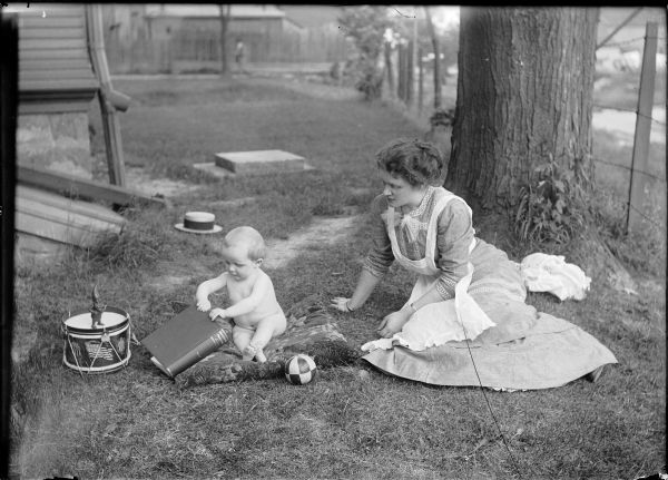 "Beatrice C. Gesell and Gerhard Gesell, Jr. play out-of-doors.  While mother watches the baby sits on a pillow playing with a volume titled ""Educational Problems.""  Also pictured are a toy elf, a drum and a ball. The picture being taken in Ridgeway is not confirmed."