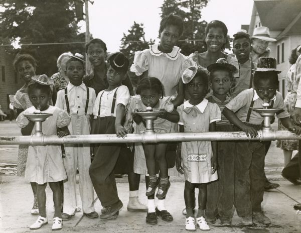 A group of African American children drinking from water fountains, or bubblers as they are frequently known in Milwaukee, at the Wisconsin State Fair.