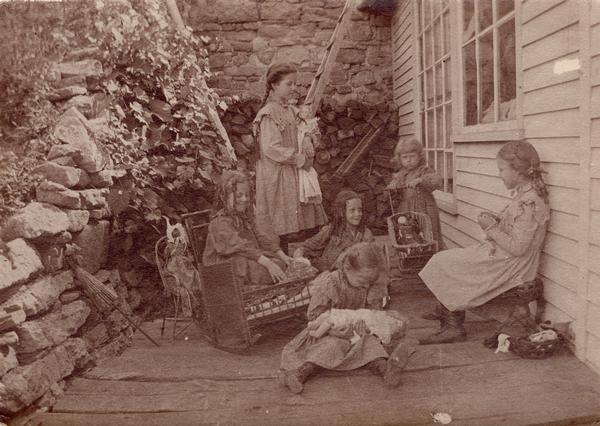 Six young girls playing with dolls on a porch.