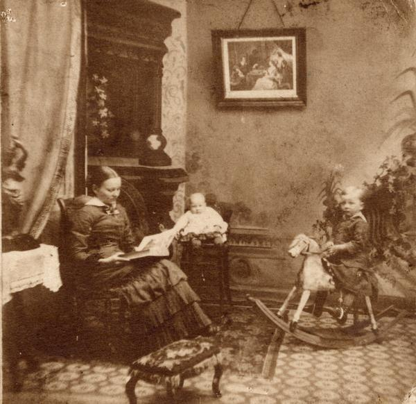 Woman sitting in a chair reading, with one child on a rocking horse and another child in a high chair.