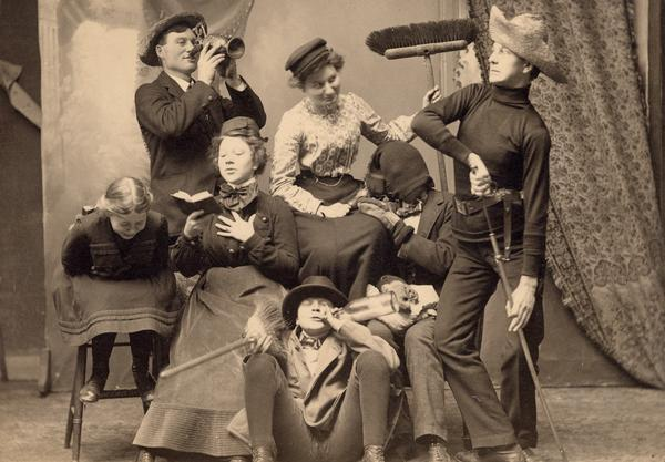 The Gesell family in costume with broom, sword, and other props for a humorous picture. Family members identified as follows: Gerhard Jr. (drinking from pitcher), Mrs. Gesell (seated with broom), Arnold (drawing sword-Civil War vintage), Gerhard Sr. (with stocking hat over head and mittens), Wilma (with book), Bertha (doubled over laughing), and Robert (sitting on floor with broom and bottle).