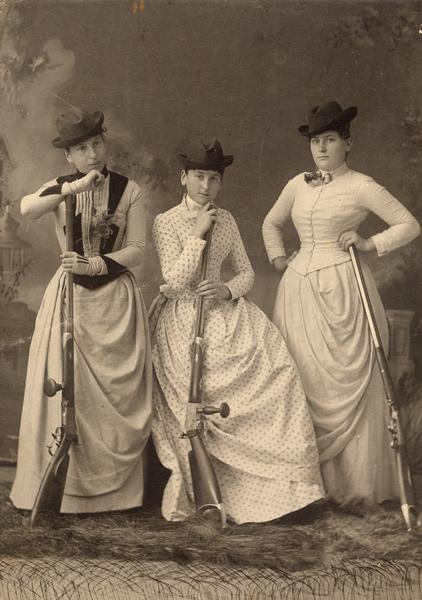 "Studio portrait in front of a painted backdrop of Emma Protz, an unidentified woman (likely Julia Protz), and Clara Tester posing with ""schuetzen-rifles."" The Alma Schuetzenverein was a target shooting society organized on the same basis as those found in Switzerland at the time."