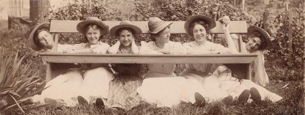 Six young women posing playfully beneath a bench.