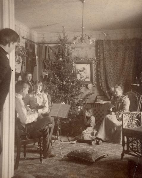 A family sits around a Christmas tree playing music and singing.