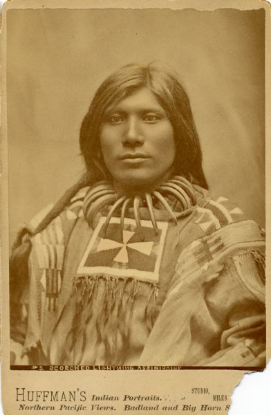 Waist-up studio portrait of Scorched Lightning (Assiniboine), member of the Sioux Nation, in traditional costume, including a bear claw necklace.