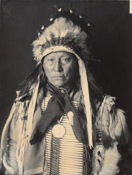 Studio portrait of Chief Mato-He-Hlogeco or Matho-Hexaloketca or Hu-Hu-Lo (Hollow Horn Bear or Bones) or Hoo-Hoo (The Bone), Son of Maza-Pankisko (Iron Shell), in native dress with peace medal, headdress and breastplate. Part of Siouan (Sioux) and Brule Tribes.
