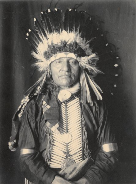 Portrait (Front) of Maga Ska (White Swan), Called Joseph H. Ellis, Jr?, in partial native dress with two peace medals, headdress and breastplate. Part of Siouan (Sioux) and Yankton Tribes.