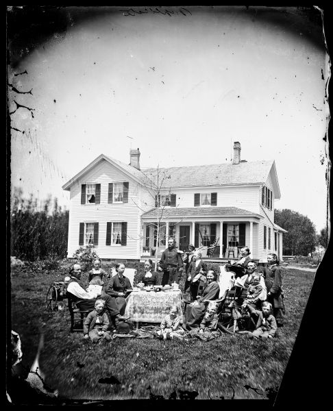 "Norwegian family posing with their household possessions, in front of their home. The man dressed in military uniform is a Civil War veteran. Madison, Wisconsin (area), ca. 1870-1879.  The family is in a yard around a table adorned with a lace cloth.  Coffee cups, figurines and books are on the table.  On the left is a man holding a newspaper that says ""Norden.""  A baby sits in a buggy behind him.  In the rear is a man dressed in a military uniform and, behind him, a man with a rake. On the right is a woman with a tray of beverages and, in front, a rocking horse."