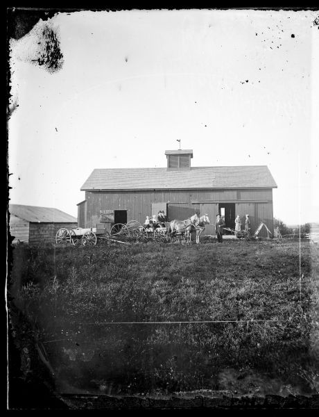 People are sitting in a horse-drawn wagon and standing next to farm machinery, including a dump rake and a hay mower.  A barn is behind them.