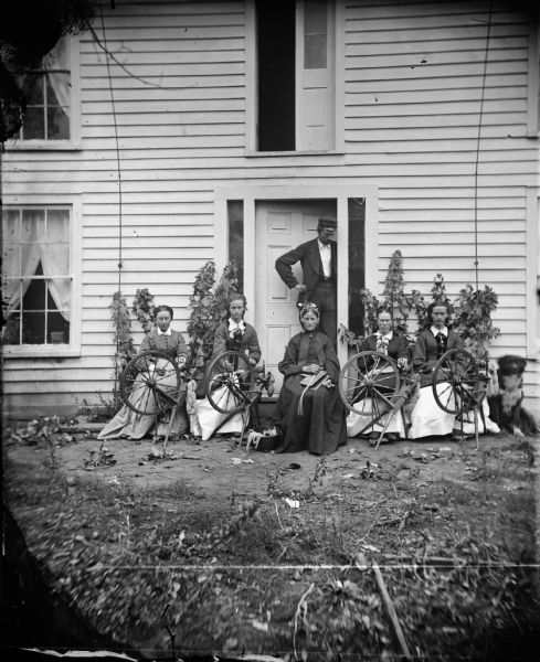 Amund Rustebakke, standing in doorway, and Siri Rustebakke, center, sitting, in front of a house with her daughters and daughter-in-law and four spinning wheels. A dog is sitting nearby on the right. [corrected from Herman to Amund 6/2010]