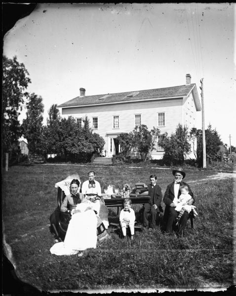 The William McFarland family is gathered around a table covered with books, pine cones, glassware and flowers in front of their Exchange Street house in McFarland, Wisconsin. Left to right are Mrs. Sela Nelson McFarland holding Joseph; Martha, Edward, John; Mr. McFarland holding Mary, a step-daughter. A telegraph pole and wires are in the right background.