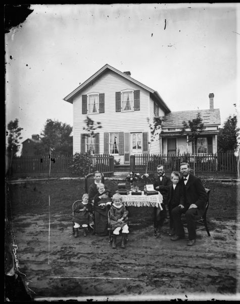 "A family seated around a table that has a fringed cloth. The children sit in small chairs and a woman holds a baby. The frame house behind a picket fence has a ""ten commandments"" type window in its front door, small windows on an addition and its front door has shutters along its side. Possibly the Anders Moldstad family."