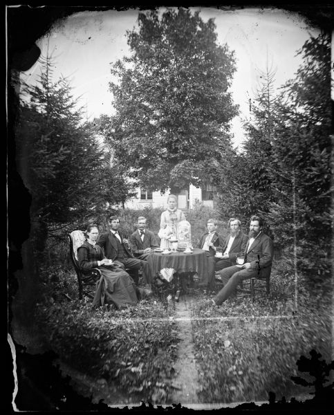 The Reverend Peter Andreas Rasmussen (1829-1898) on the right, his wife Ragnhild Holland Rasmussen on the left and some visiting gentlemen, no doubt Lutheran ministers, are seated around a table drinking coffee. A large glass flower bell dome adorns the table. The frame house behind them is obscured by trees.