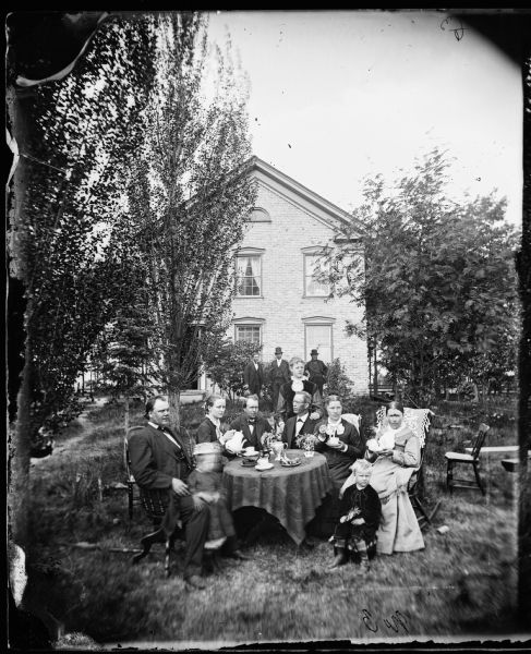 A group seated around a table in the yard drinking coffee. Pastor Even Johnson Homme (1843-1903), the founder of the Wittenberg Orphan's Home, is on the left. Mrs. Ingeborg Swenholt Homme sits at the right front. The photograph was made at the meeting of the Eastern District Norwegian Synod, held at the Immanuel Norwegian Evangelical Lutheran Church.