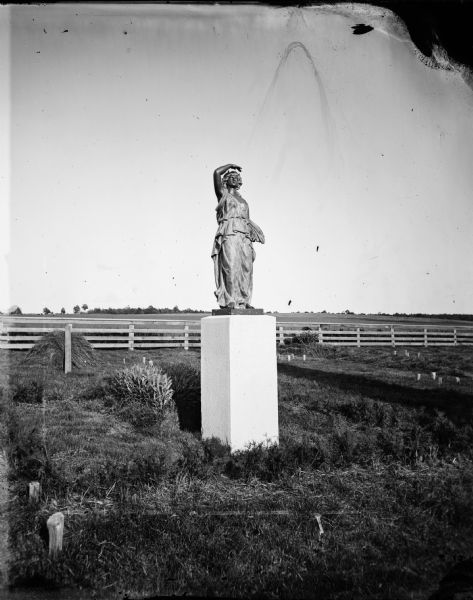 "One of the eight female figures purchased from the Chicago firm Gould Brothers and Dribblee to be used on the gate posts of the Wisconsin State Capitol fence.  Only four were used and this is possibly the extra figure, ""Candelabra."" It became a memorial marker for Mary McFarland (died April 1, 1879) in the McFarland Family plot in McFarland Cemetery."