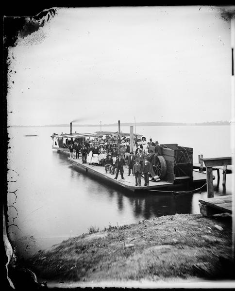 A large group of well-dressed people are standing aboard three small steamboats on Lake Monona. The boat in the foreground is a barge with a sternwheel. The two behind are sidewheel excursion boats.