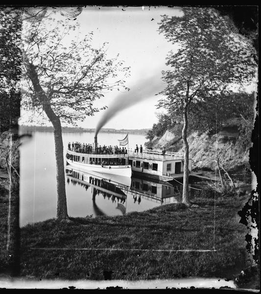 "Norwegian Sunday School Picnic at Mendota steamboat landing. Small lake steamer ""Mendota"" could reach speeds of up to 18 mph. The barge ""Uncle Sam"" was 75ft long by 25ft, and was either towed about the lake or anchored at the picnic grounds at McBrides Point. ""The Mendota"" made regular trips to Picnic Point, the University, Pheasant Branch, and the Insane Asylum."