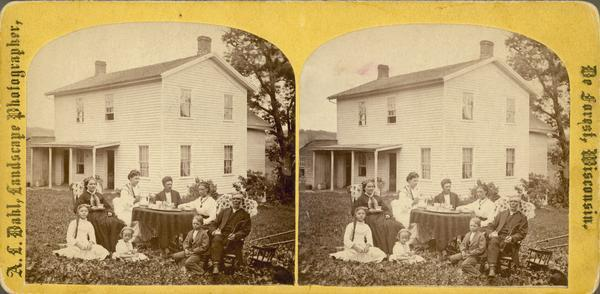 "The Reverend John N. Fjeld, pastor of the Vermont Lutheran Church, enjoying coffee and a pipe with his family. His wife Gunhild on left (it could be his second wife Ingeborg wearing a necklace and sitting on Fjeld's right). A yellow mount stereograph listed as ""Rev. J. Fjeld and family, Black Earth, Wis."" in Dahl's 1877 ""Catalogue of Stereoscopic Views."""