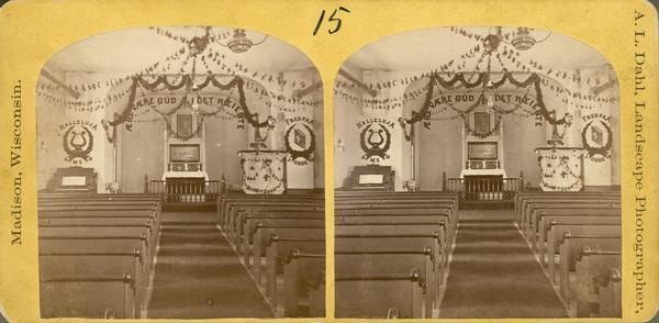 The interior of a Norwegian-American Lutheran Church decorated with garlands and religious admonitions in Norwegian.
