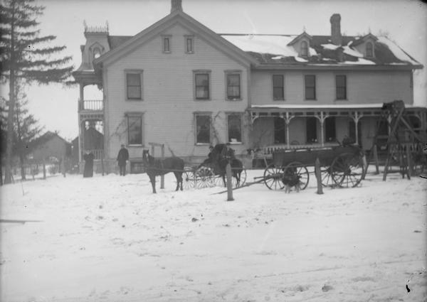 The Park Hotel, once lived in by Lewis Dahl and family. It was also the Isaac DeForest home. There is a wagon or carriage outside and snow on the top of a frame building. Two narrow windows on third floor of building, side porch and front porch with second story balcony tower type roof.