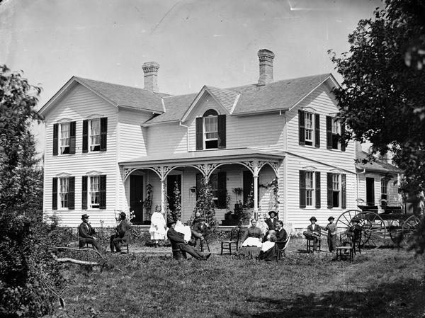 This is said to be the family of Hans Holtan (a.k.a. Austinson) posed in the yard before a frame house that has carpenter's lace on porch, two separate doors, shutters and a fan shape above window on gable. Numerous house plants are on the porch and a man sits in an unusual bucket chair holding out what appears to be a newspaper. In the 1870 census the family consisted of Hans 36, Rana 37, Austin 9, Jergen 1, Jane 5, John 7 and Ole 4 1/2. Holtan's sister Rachel 38 also lived there as well as two male farm laborers.