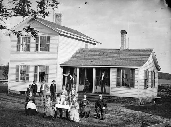 A family of sixteen in yard around table set for coffee. Three men are in the background, one holding a shotgun. There is a frame house with shutters and stone foundation behind them.