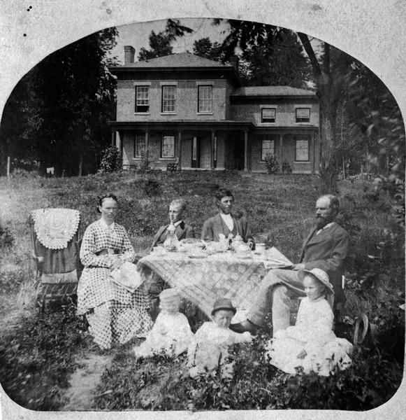 Halle Steensland and his wife Sophia pose with their five children at the family home, later located at 733 Lakewood Boulevard, Village of Maple Bluff. (The house and farm were later owned by Robert M. La Follette, Sr.) The two older boys, Halbert and Henry, sit behind a table set for coffee and covered with a beautiful lace table cloth. On the ground before the table sit the younger children, Edward, Morton and Helen. A carriage and outbuilding, probably a carriage house, are visible.