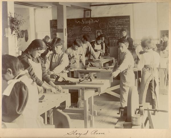 Students working in a sloyd room at the Indian Industrial School.  A sloyd is a type of wood-carving knife.