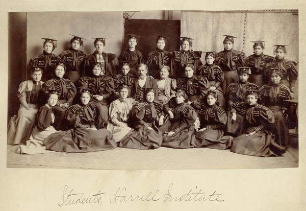 Harrell International Institute female students, posed in caps and gowns.