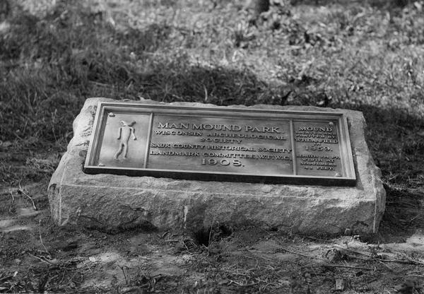 "Historic site marker to commemorate Man Mound and to mark Man Mound Park.  The inscription reads ""Man Mound Park.  Mound located and platted by W.H. Canfield in 1859.  Length 214 ft., width at shoulders 48 feet.""  The tablet was unveiled on August 7, 1908."