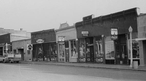 Canal Street with the businesses that were built after the fire.  Ford stepside truck on the left side of the photo.  Businesses with three Coca-cola signs, a Blatz sign, and a Pabst Blue Ribbon sign.