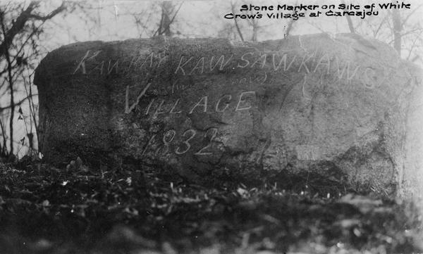 "Close-up view of an etched stone that says, ""Kaw Kay Kawsawkaws (White Crow) Village 1832."""