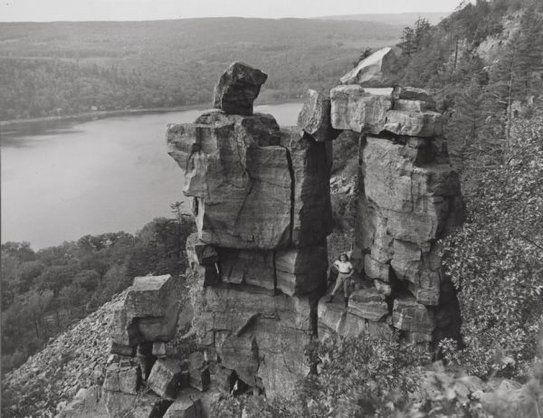 View of the rock formation on a cliff overlooking the lake.  A little girl stands in the doorway.