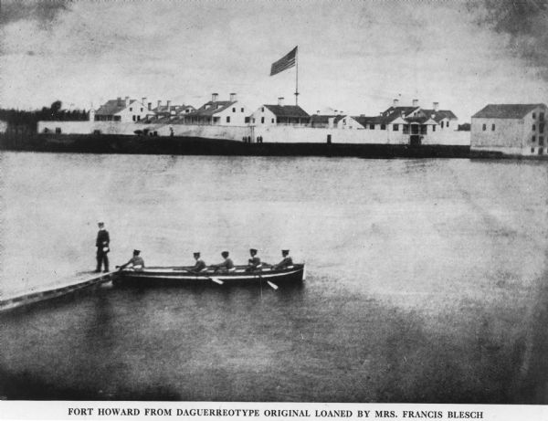 View of five soldiers rowing in a boat, beside a dock, with another soldier standing on the dock. The fort is visible in the background, complete with the fortified walls, and people standing in the front of the walls. The American flag stands above the fort in the center of the image.