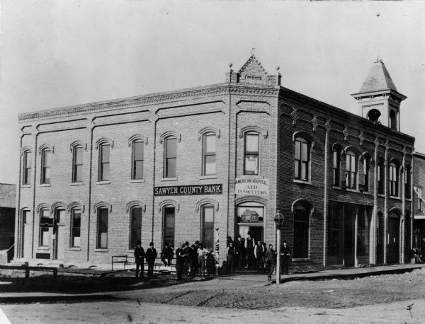 View of the Sawyer County Bank with a group of people posed near its doorway. The Sawyer County Bank was organized on March 3, 1884 with a capital stock of $200,000.  The street in front of the bank was paved in 1896.