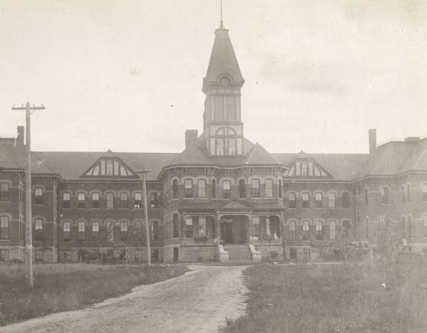 View of the Marathon County Asylum with dirt road leading to the main entrance.