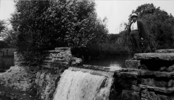 View of a man standing near the pond and spillway on the grounds of Taliesin, Frank Lloyd Wright's residence and architectural school complex. Taliesin is located in the vicinity of Spring Green, Wisconsin.