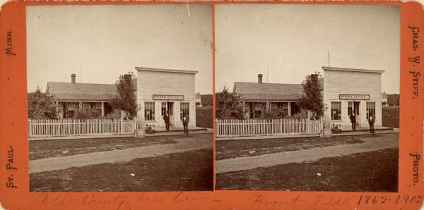Exterior stereograph of the Polk County Press Office with three men standing and three children seated on its front porch.