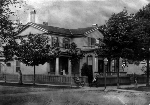 View from street towards the J.H. Kelley house. The home was located at the Northwest corner of Wisconsin Avenue and 8th Street, which is now the Southeast corner of the block containing the present Racine County Court House. James H. Kelley - Died 1905 at his residence. He was the President of The Racine Silver Plate Company, manufacturers of gold and silver plated ware, Britannia ware, cutlery, etc. Their goods were classed with those of Rogers & Co., and other well known Eastern manufacturers. He also owned Kelley, Weeks & Co. 927 N. Erie Street. Wholesale Lumber Dealer.