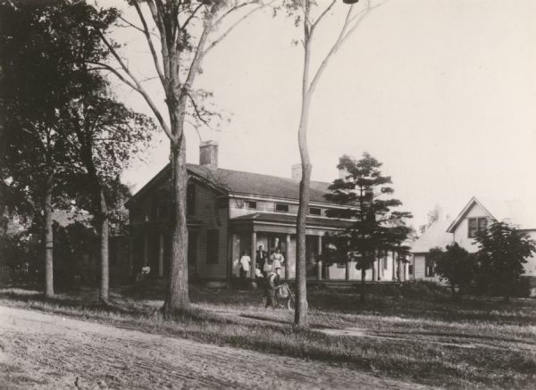 John Meade's residence. The family is standing on the front porch for a group portrait, while an individual pushes a bicycle.