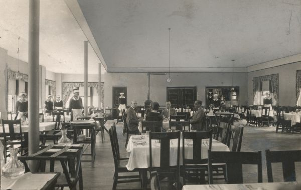 Interior of the Sherwood Forest Hotel dining room.  Men and women are seated at a table for a meal, and the uniformed waitstaff stand to the left.