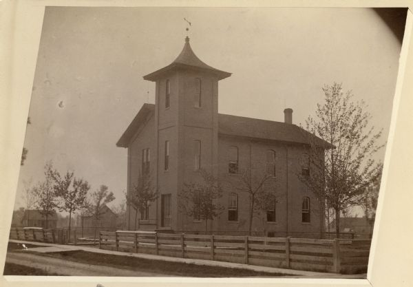 Side view of Fourth Ward School, surrounded by wooden fence.