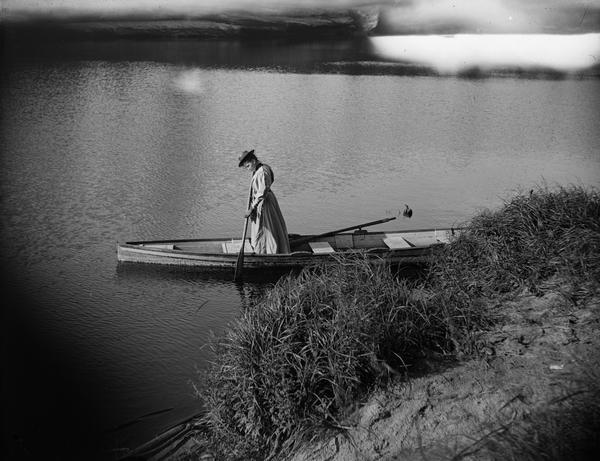 Woman standing in a rowboat near shore, testing the water with an oar.
