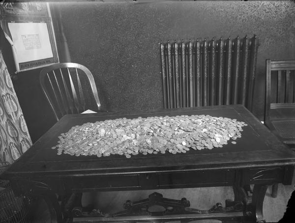 Pile of dimes spread on a table with chair to right and behind, near radiator.