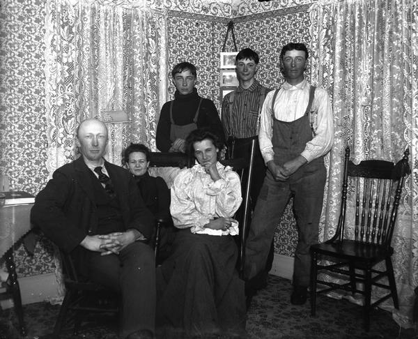 "A farm family posing in their living room. Sitting from left to right is John Dietrich (1874-1947), Grace Bowman (1879-1964), and Mrs. Lizzie Macke Dietrich (1880-1933). Standing behind them are Philip (b. 1880), George (b. 1883) and Julius (1885-1952) Nortman.   Like others in Black River Falls, Dietrich was accused of pro-German sympathies during World War I. He was persecuted by being forced to ride on a log up and down Main Street, etc. On Armistice Day, 1918, a group went to his place in the country, put him in a truck, and made him kiss the United States flag.  Caption from Classified File reads: ""Farm family posing in living room. John Diedrich, Grace Bowman and Mrs. Diedrich (Lizzie Macke),--seated. Standing: Philip, George and Julius Nortmann. (Mrs.?) Rozmanoski (owner?) of the Pines Hotel is (Diedrich's) daughter. Like others in this community, Diedrich was accused of pro-German sympathies during the first World War and he was persecuted by being forced to ride a log up and down Main St., etc. On Armistice Day, 1918, a group went to his place out of town, got him in a truck and made him kiss the U.S. flag. (They ? ""put the Gerhardt boys on a stone boat"")."